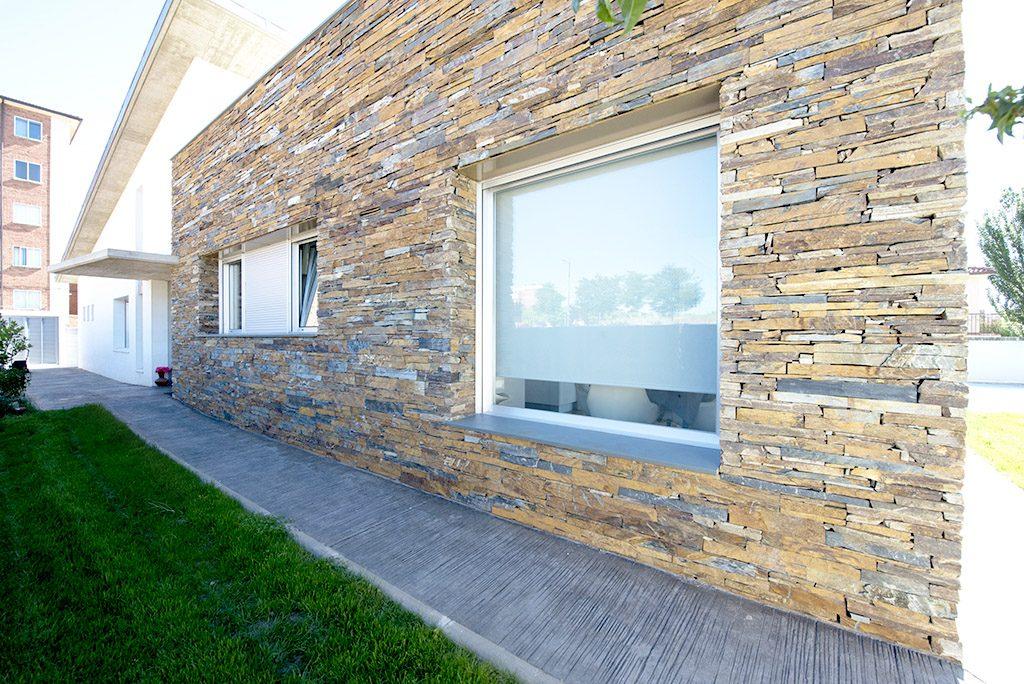 Ventana de aluminio en fachada de piedra